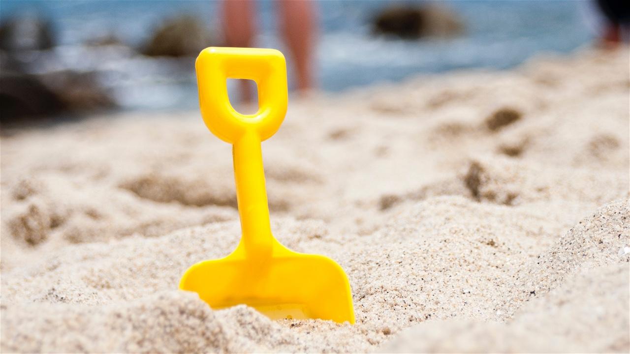 Een gele schep in het zand.